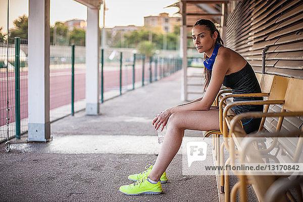 Junge Frau sitzt auf Bank und ruht sich aus