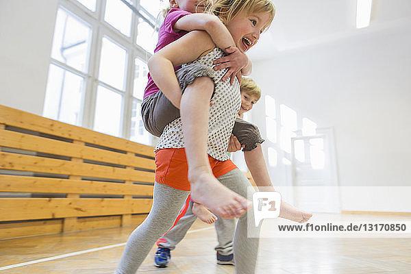Kinder mit Huckepack-Rennen in der Schulhalle