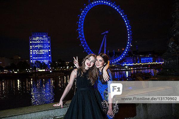 Porträt von zwei Freundinnen  die nachts mit dem London Eye posieren  London  UK