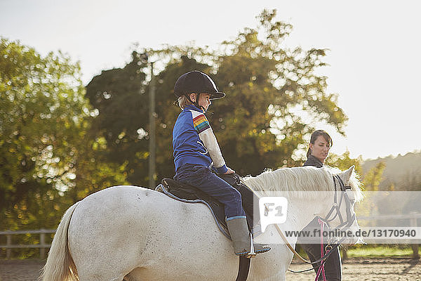 Instructor leading boy riding pony in equestrian arena