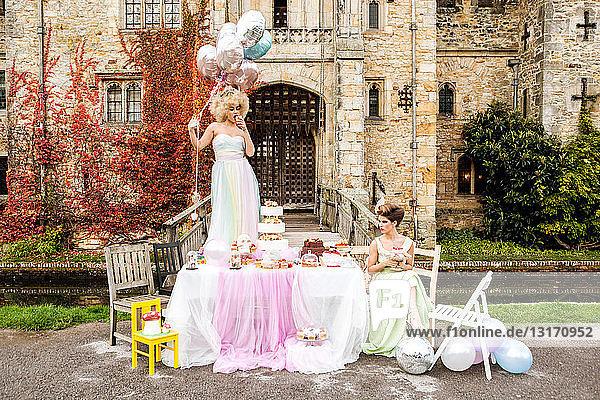 Braut am Tisch stehend  Brautjungfer sitzend