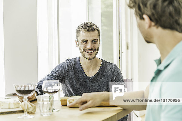 Two young men chatting at table at party in dining room