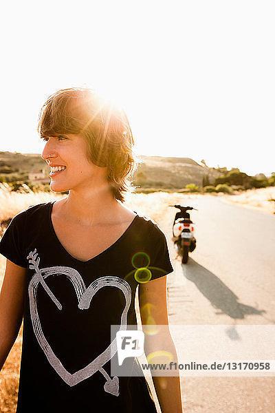Lächelnde Frau geht auf ländlicher Straße