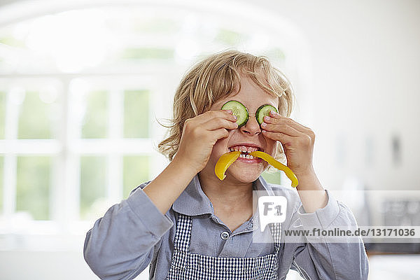 Boy playing with vegetables in kitchen
