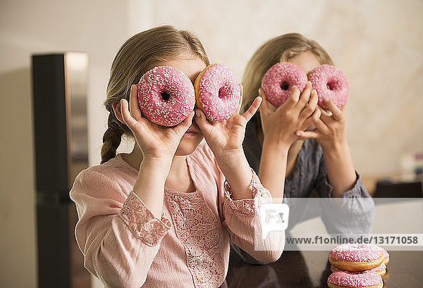 Portrait of two sisters with doughnut holes over their eyes