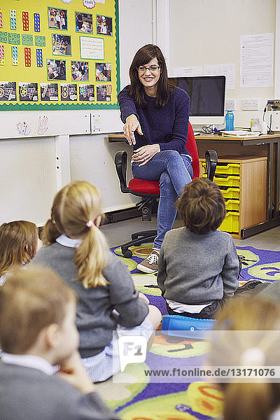 Teacher pointing to children sitting on floor in elementary school classroom