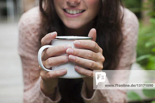 Nahaufnahme einer jungen Frau  die im Garten sitzt und Kaffee trinkt