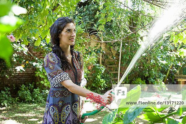 Frau gießt Pflanzen im tropischen Garten