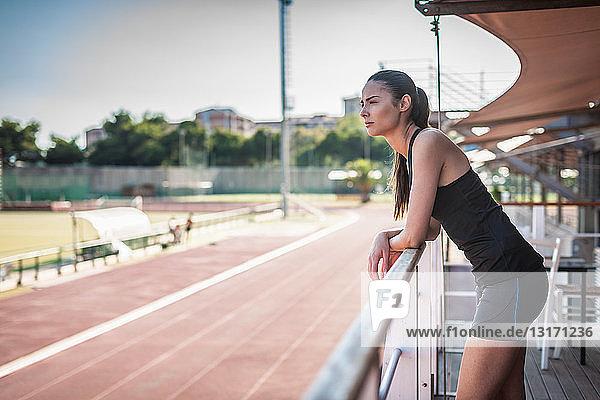 Junge Frau lehnt an Geländer an der Rennstrecke