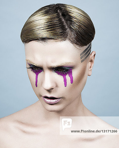 Junge Frau mit kurzer Frisur und aus den Augen strömender farbiger Farbe