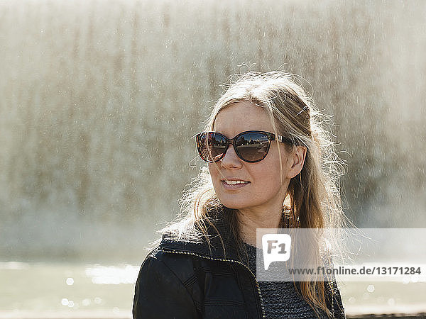 Portrait of mid adult woman wearing sunglasses in front of fountain on Montjuic Hill  Barcelona  Spain
