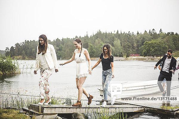 Multi-ethnische Freunde gehen am Wochenende auf dem Steg über dem See