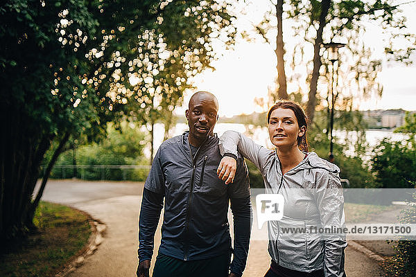 Portrait of confident male and female athletes standing on road in park