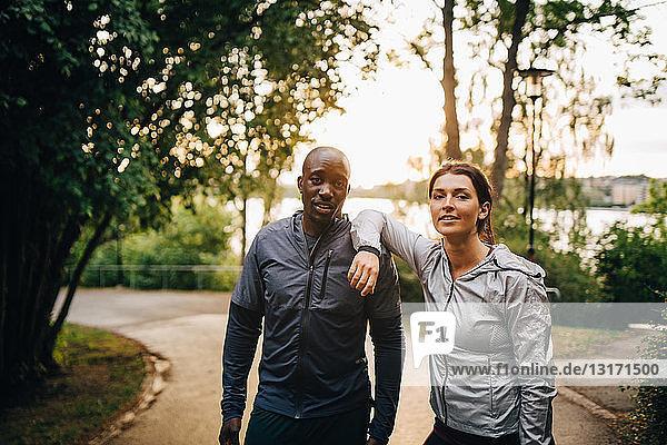 Porträt selbstbewusster männlicher und weiblicher Athleten  die im Park auf der Straße stehen