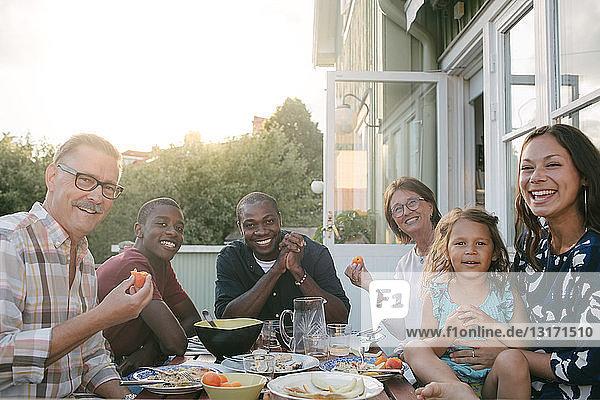 Porträt einer lächelnden Mehrgenerationen-Familie beim Mittagessen bei Tisch auf der Veranda