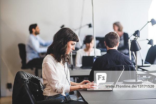 Geschäftsfrau benutzt Laptop  während sie im Kreativbüro am Schreibtisch sitzt