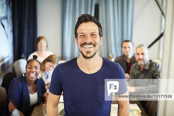 Porträt eines selbstbewussten Geschäftsmannes im Stehen  während seine Kollegen im Hintergrund im Amt sind