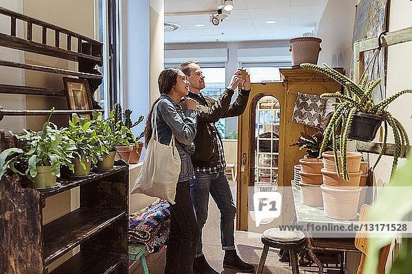 Ehepaar fotografiert Wanddekoration im Stehen in einer Boutique