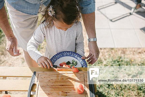 Mädchen legt Tomatenscheiben mit dem Messer in einen Teller  während sie während der Gartenparty beim Großvater am Tisch steht