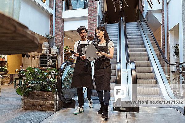 Männliche und weibliche Kollegen diskutieren beim Gehen gegen eine Rolltreppe in einer Boutique