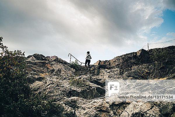 Niedrigwinkelansicht einer Athletin  die auf einem Hügel auf Felsen klettert  gegen den Himmel