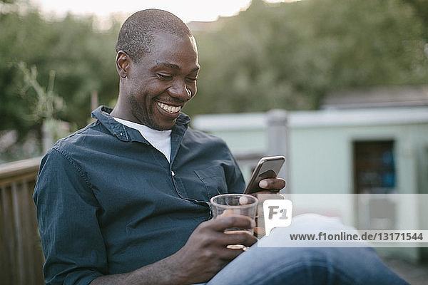 Lächelnder mittelgroßer Mann  der ein Mobiltelefon benutzt  während er Glas auf der Veranda hält