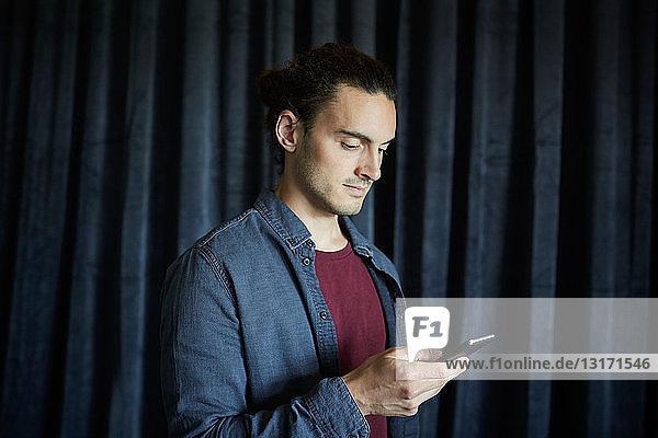 Kreativer Geschäftsmann benutzt Mobiltelefon gegen Vorhang im Büro
