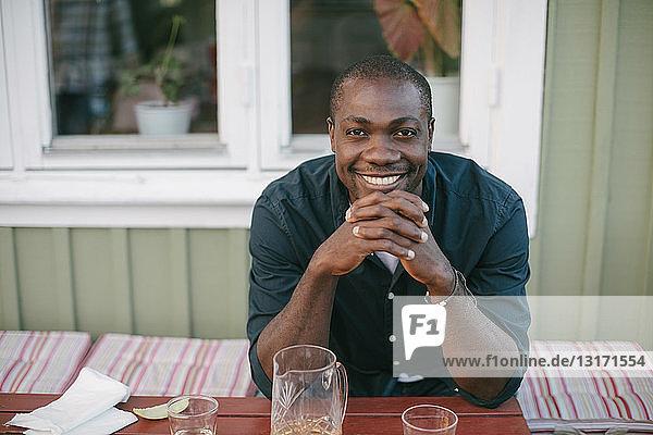 Porträt eines lächelnden  mittelgroßen Mannes  der am Tisch auf der Veranda sitzt