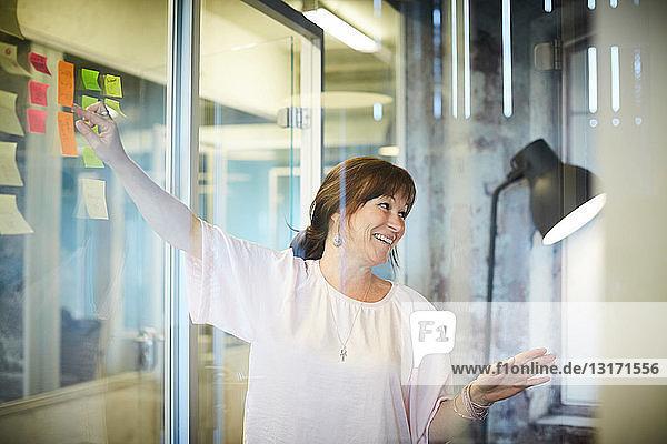 Lächelnde Geschäftsfrau diskutiert  während sie im Kreativbüro auf Haftnotizen zeigt