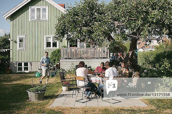 Mehrgenerationen-Familie isst während der Gartenparty auf der Terrasse