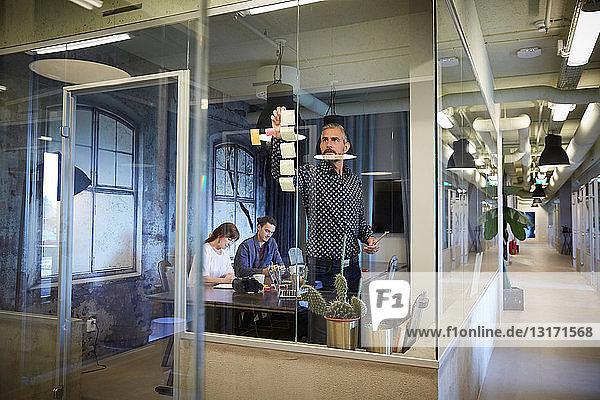 Kreative Geschäftsleute  die im Sitzungssaal arbeiten  durch Glas gesehen