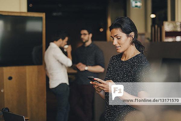 Textnachrichten von Geschäftsfrauen auf Smartphones mit Kollegen im Hintergrund im Büro