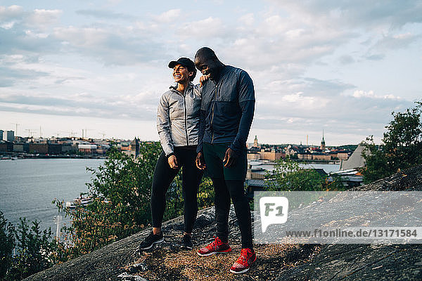 Full length of happy male and female athlete standing on hill against sky