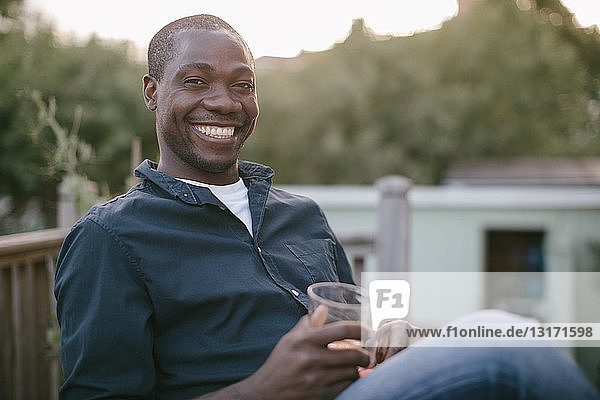 Portrait of smiling mid adult man holding glass while sitting at porch