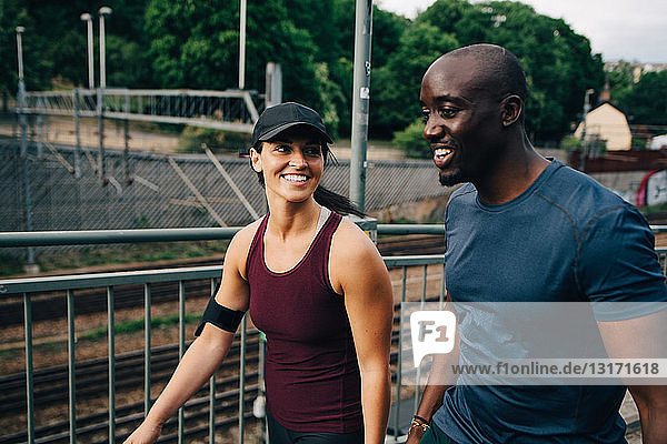 Smiling male and female athlete walking on footbridge in city