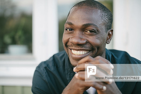 Porträt eines lächelnden  mittelgroßen  erwachsenen Mannes mit gefalteten Händen