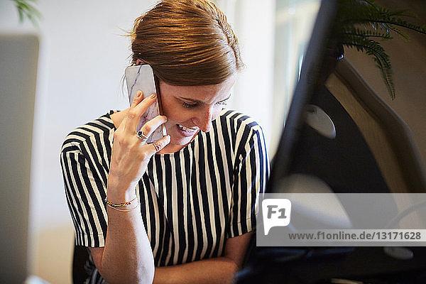Kreative Geschäftsfrau  die im Büro am Computerschreibtisch sitzt und mit dem Handy telefoniert