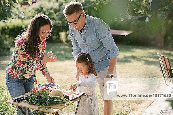 Mädchen schneidet Essen  während sie bei Mutter und Großvater am Tisch im Hinterhof steht