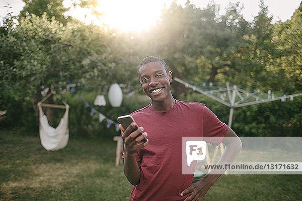Porträt eines lächelnden Jungen mit Handy in der Hand  der während einer Gartenparty im Hinterhof steht