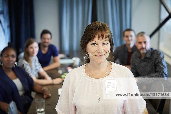 Porträt einer selbstbewussten reifen Geschäftsfrau im Stehen  während die Kollegen im Hintergrund im Amt sind