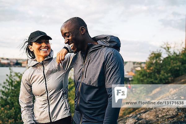 Smiling male and female athlete standing on hill against sky