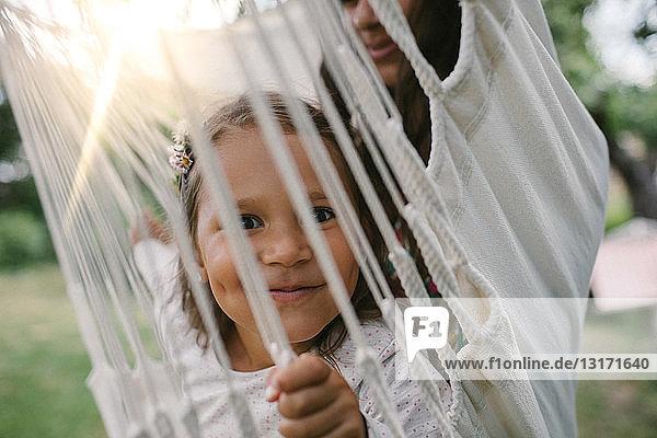 Porträt eines lächelnden Mädchens  das durch Seile gesehen wird  während es mit seiner Mutter auf einer Hängematte im Hinterhof schwingt