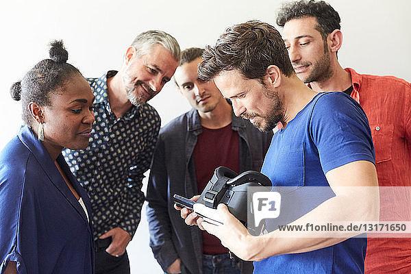 Geschäftsmann hält Virtual-Reality-Simulator in der Hand  während er Kollegen im Kreativbüro sein Handy zeigt