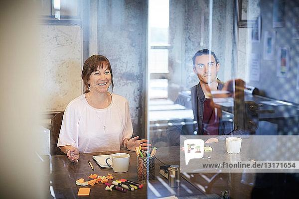 Kreative Geschäftsleute sitzen im Sitzungssaal durch Glas gesehen
