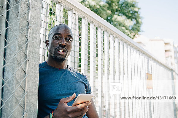 Portrait of sportsman using mobile phone while leaning on railing at bridge