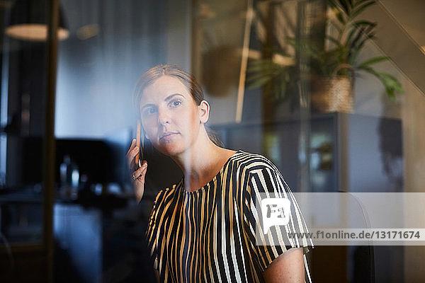Kreative Geschäftsfrau beim Telefonieren mit dem Handy durch Glas im Büro gesehen
