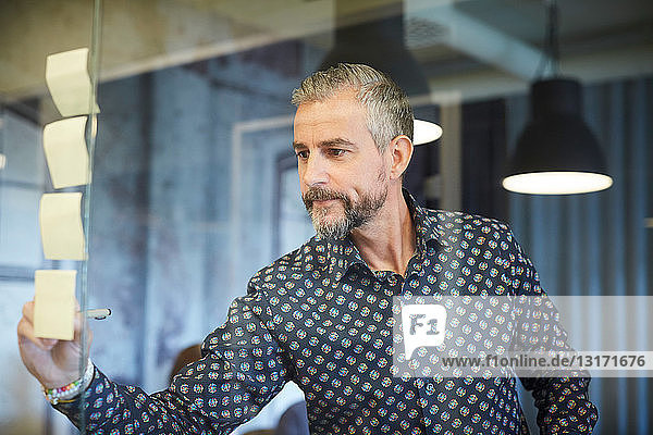 Reifer Geschäftsmann schreibt im kreativen Büro auf Klebezettel  der auf Glas geklebt wird