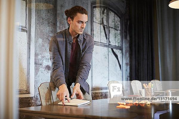 Junger Geschäftsmann nimmt Spiral-Notizbuch vom Konferenztisch im Büro