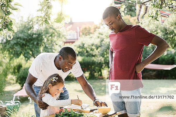Junge sieht Vater an  der seiner Schwester bei der Zubereitung von Essen am Tisch während einer Gartenparty hilft