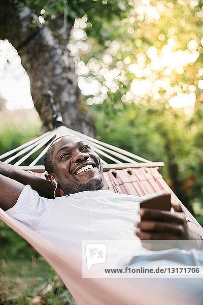 Lächelnder mittelgroßer Mann  der über sein Mobiltelefon Musik hört  während er sich auf einer Hängematte im Hinterhof entspannt
